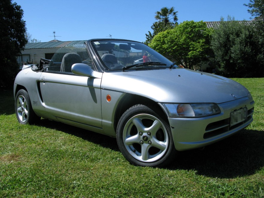 Silver Honda Beat on the grass in the sun with the top down.